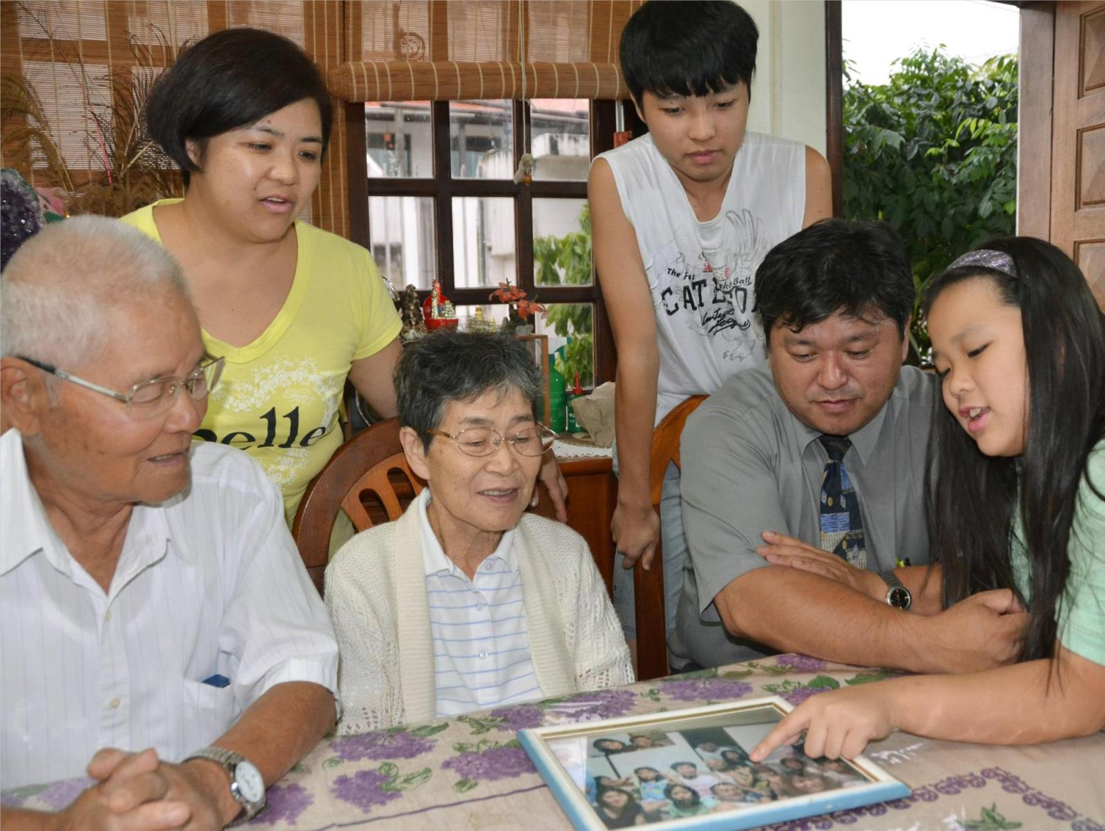 People of Japanese descent look at family photos in Piedade, Brazil, in March 2014. The vast majority of young people belo<em></em>nging to the Japanese diaspora around the world want to make co<em></em>nnections with Nikkei in other countries, a survey has shown.   KYODO